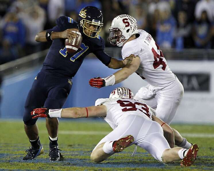 Chase Thomas (right) and Trent Murphy sack UCLA's Brett Hundley.