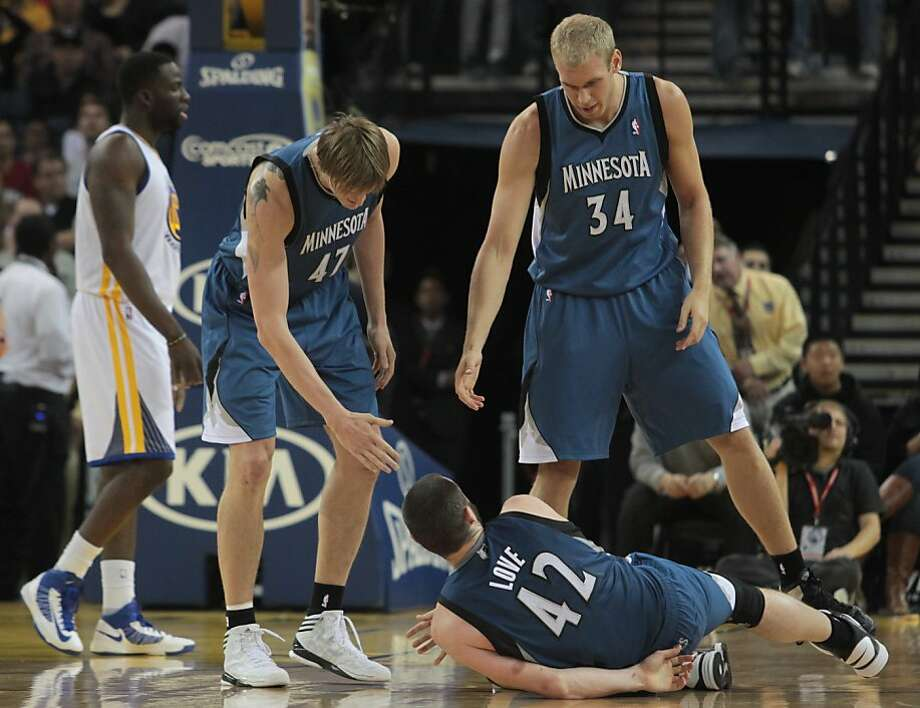 Minnesota Timberwolves' Kevin Love (42) is helped off the floor by teammates Andrei Kirilenko (47), left, and  Greg Stiemsma (34) in the second half of an NBA basketball game against the Warriors in Oakland, Calif., Saturday, Nov. 24, 2012. The Warriors won 96-85. (AP Photo/Mathew Sumner) Photo: Mathew Sumner, Associated Press