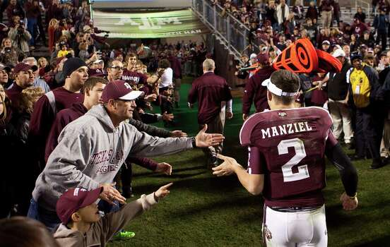 Texas A&M quarterback Johnny Manziel (2) is greeted by fans as he runs off the field after the Aggies beat Missouri, Saturday, Nov. 24, 2012, in Kyle Field in College Station. Photo: Nick De La Torre, Houston Chronicle / © 2012  Houston Chronicle
