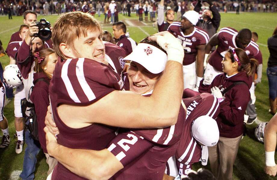 Texas A&M defensive lineman Spencer Nealy (99) hugs Texas A&M quarterback Johnny Manziel (2) after beating Missouri, Saturday, Nov. 24, 2012, in Kyle Field in College Station. Photo: Nick De La Torre, Houston Chronicle / © 2012  Houston Chronicle