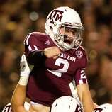 Texas A&M quarterback Johnny Manziel (2) is lifted by the offenseive line after running for a touchdown during the third quarter of a NCAA football game, Saturday, Nov. 24, 2012, in Kyle Field in College Station.
