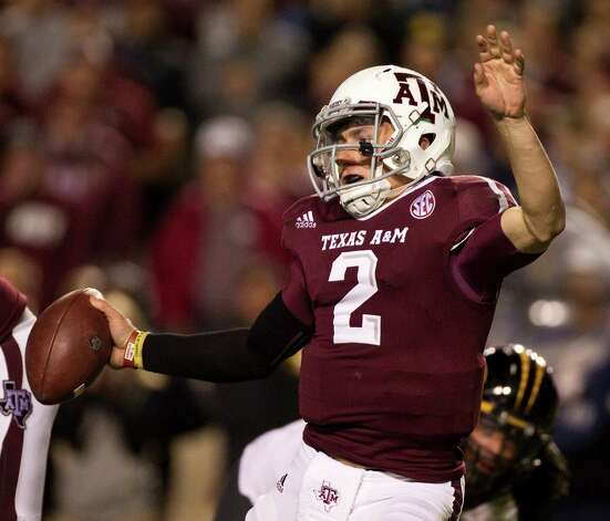 Texas A&M quarterback Johnny Manziel (2) wiggles out of being tackled by a Missouri defender during the third quarter of a NCAA football game, Saturday, Nov. 24, 2012, in Kyle Field in College Station. Photo: Nick De La Torre, Houston Chronicle / © 2012  Houston Chronicle