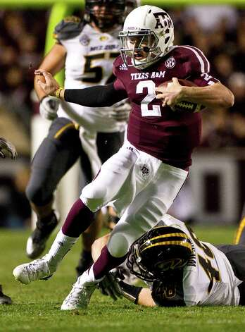 Texas A&M quarterback Johnny Manziel (2) scrambles for extra yards in the Missouri defense during the first quarter of a NCAA football game, Saturday, Nov. 24, 2012, in Kyle Field in College Station. Photo: Nick De La Torre, Houston Chronicle / © 2012  Houston Chronicle