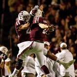 Texas A&M defensive back Dustin Harris (22) and Texas A&M quarterback Johnny Manziel (2) celebrate after Manziel threw a touchdown pass during the second quarter of a NCAA football game, Saturday, Nov. 24, 2012, in Kyle Field in College Station.