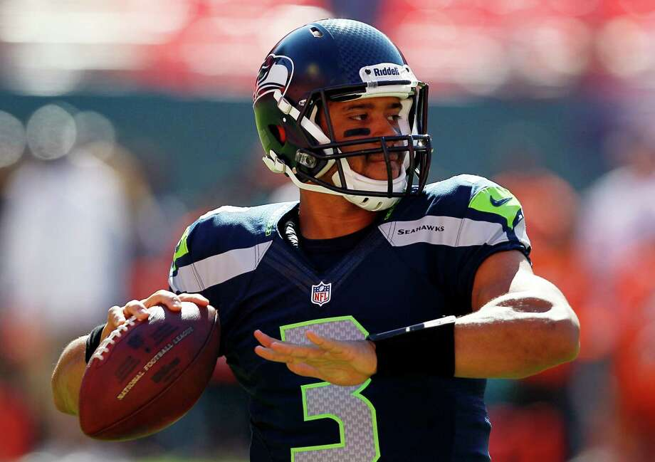 Seattle Seahawks quarterback Russell Wilson warms up before an NFL football game against the Miami Dolphins,