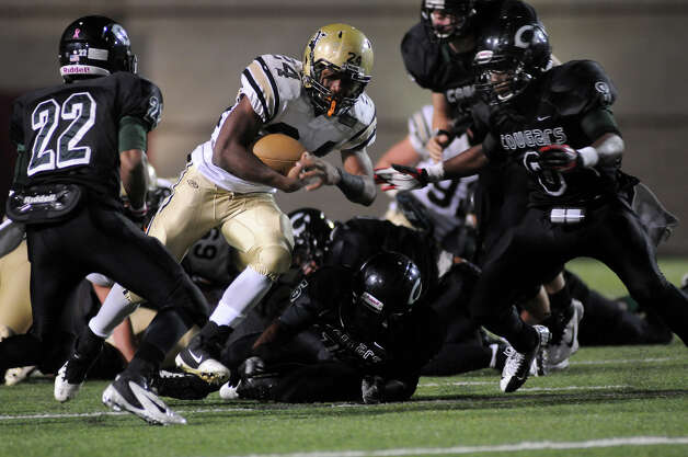 Nederland Junior running Kendrick Hopkins, center, splits a pair of Pflugerville Connally defenders during their game at Woodforest Stadium in Shenandoah on Friday. Photo by Jerry Baker
