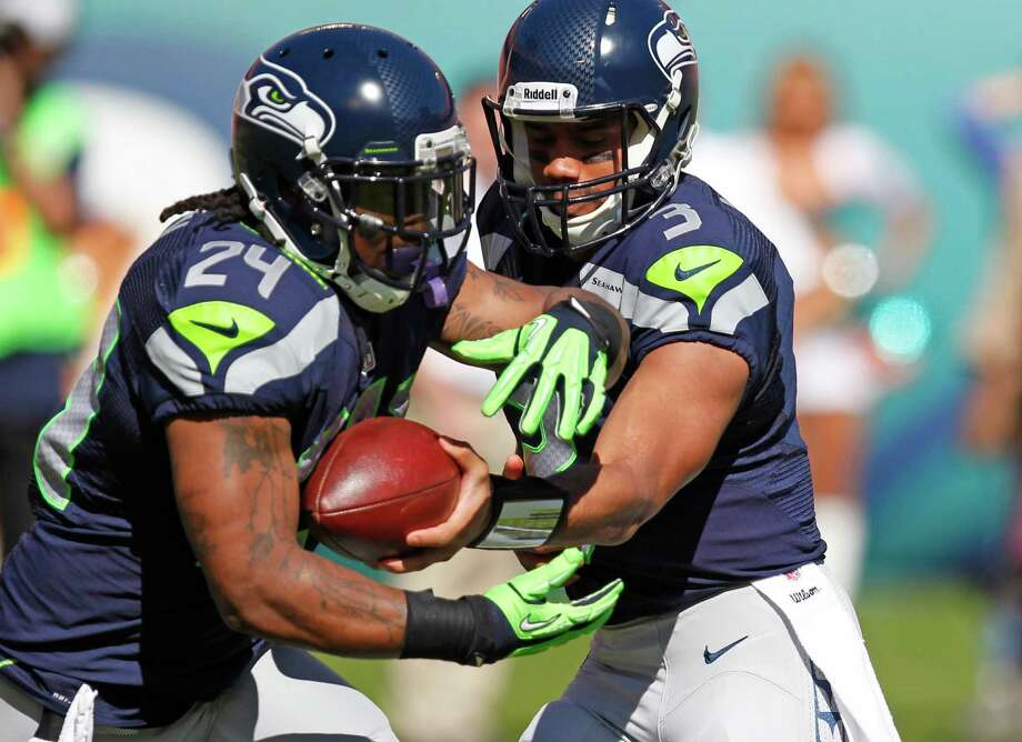 Seattle Seahawks quarterback Russell Wilson (3) hands off the ball to  running back Marshawn Lynch during the first half of an NFL football game against the Miami Dolphins, Sunday, Nov. 25, 2012 in Miami. Photo: AP
