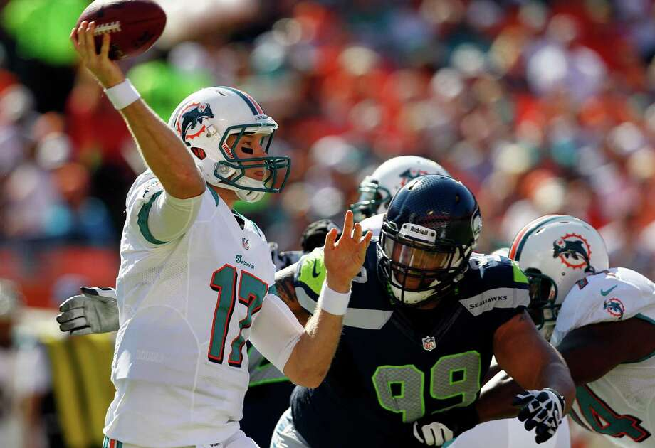 Miami Dolphins quarterback Ryan Tannehill (17) throws as Seattle Seahawks defensive tackle Alan Branch closes in during the first half of an NFL football game against the Miami Dolphins, Sunday, Nov. 25, 2012 in Miami. Photo: AP