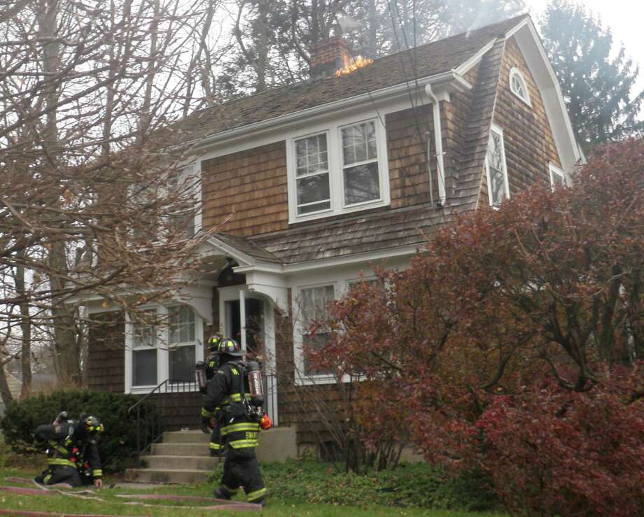 A small patch of flames is visible on the roof of this Washington Avenue house, where firefighters were dispatched after embers from the chiminey apparently sparked the fire.  Westport CT 11/25/12 Photo: Westport Fire Department / Westport News contributed