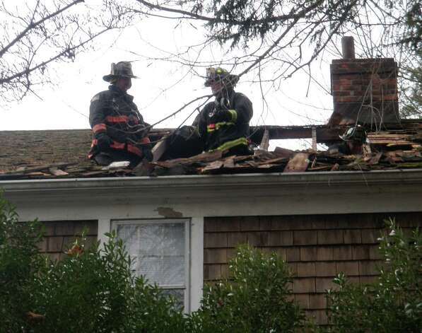 Firefighters inspect damage to the roof of a Washington Avenue home where chimney embers apparently sparked a fire Sunday morning.  Westport CT 11/25/12 Photo: Westport Fire Department / Westport News contributed