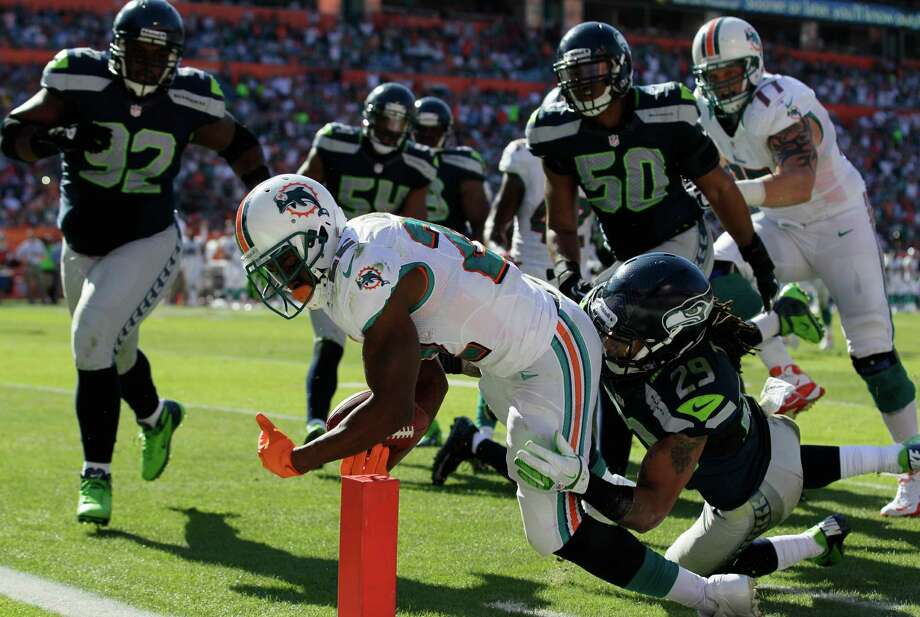 Miami Dolphins running back Reggie Bush (22) stretches for a touchdown as Seattle Seahawks free safety Earl Thomas (29) attempts to tackle during the first half of an NFL football game Sunday, Nov. 25, 2012 in Miami. Photo: AP