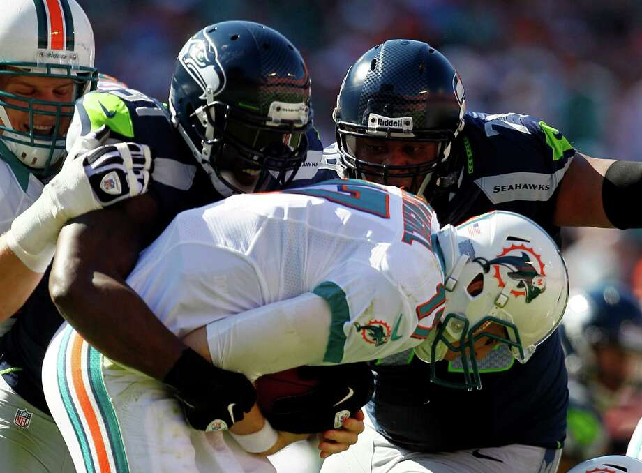 Seattle Seahawks defensive end Chris Clemons (91), left, and  Red Bryant (79) sack Miami Dolphins quarterback Ryan Tannehill (17) during the first half of an NFL football game on Sunday, Nov. 25, 2012, in Miami. Photo: AP
