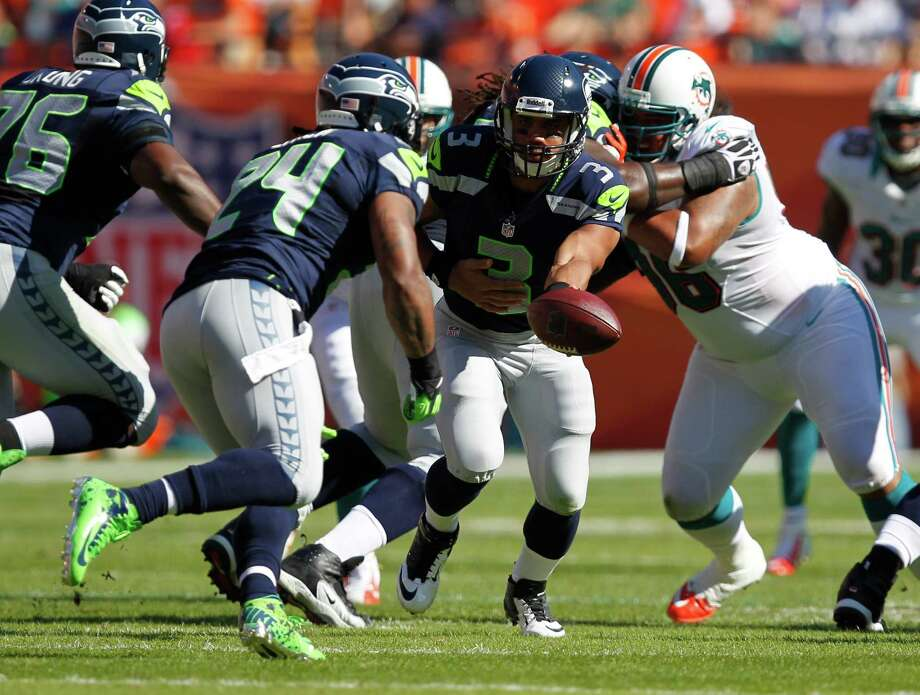Seattle Seahawks quarterback Russell Wilson (3) hands the ball to running back Marshawn Lynch (24) during the first half of an NFL football game Sunday, Nov. 25, 2012 in Miami. Photo: AP
