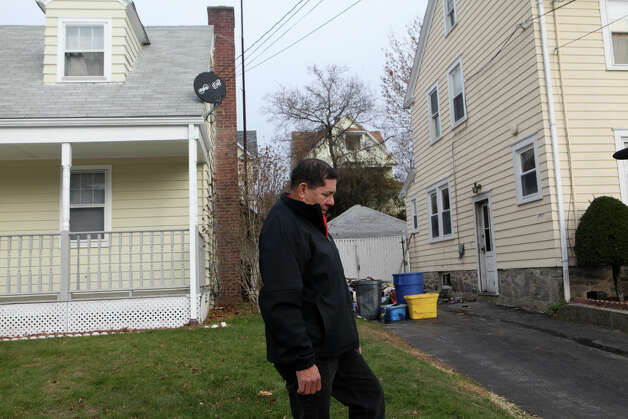 Juan Carlos Saravia stands in between his home, left, and the home of his neighbors , whom he helped out of their smoked filled house, on Wood Ave. in Bridgeport, Conn. on Monday morning, November 25, 2012. The neighbors, Rudy and Eunice Polanco and their two daughters, climbed down a ladder from their second story bathroom when their house filled with smoke from a basement fire. Photo: BK Angeletti, B.K. Angeletti / Connecticut Post freelance B.K. Angeletti
