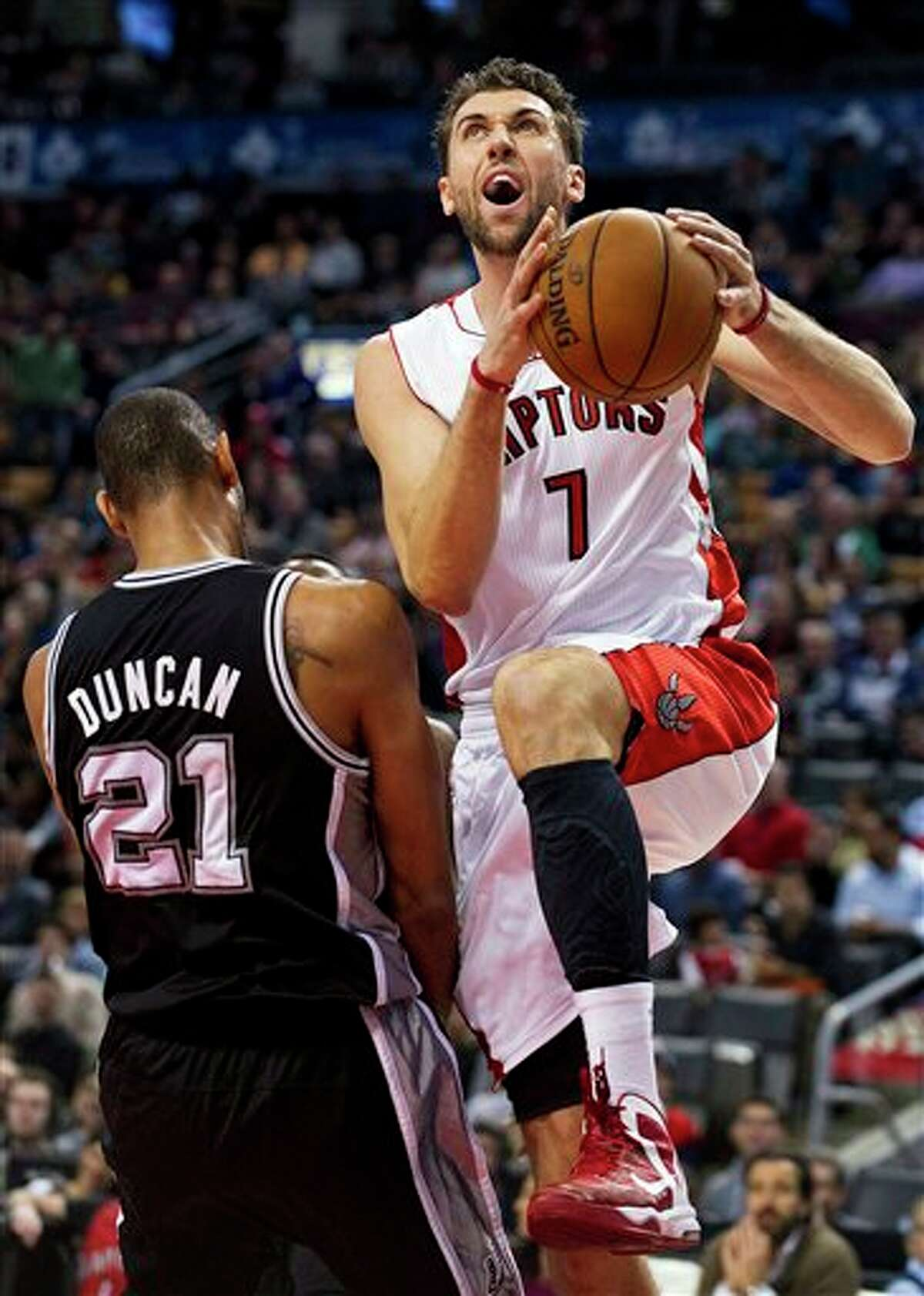 Toronto Raptors' Andrea Bargnani (7) draws a foul driving to the basket against San Antonio Spurs' Tim Duncan (21) during the first half of an NBA basketball game, Sunday, Nov. 25, 2012, in Toronto. (AP Photo/The Canadian Press, Aaron Vincent Elkaim)