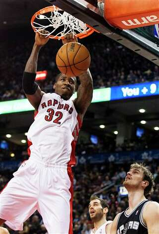 Toronto Raptors' Ed Davis (32) dunks as San Antonio Spurs' Tiago Splitter, bottom right, watches during the first half of an NBA basketball game, Sunday, Nov. 25, 2012, in Toronto. (AP Photo/The Canadian Press, Aaron Vincent Elkaim) Photo: Aaron Vincent Elkaim, Associated Press / The Canadian Press