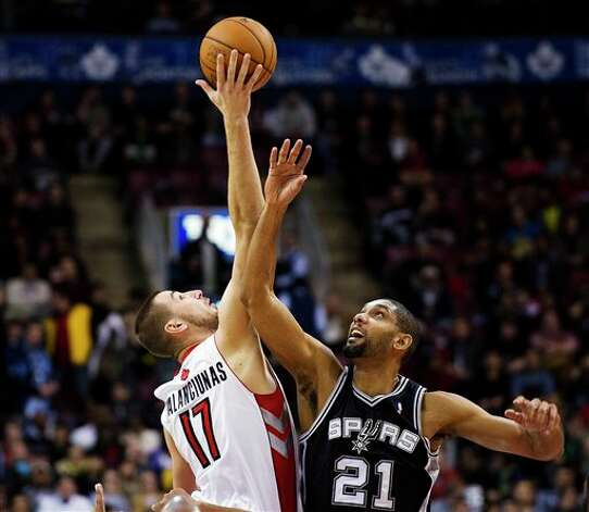 Toronto Raptors' Jonas Valanciunas (17) wins the tip-off against San Antonio Spurs' Tim Duncan (21) during the first half of an NBA basketball game, Sunday, Nov. 25, 2012, in Toronto. (AP Photo/The Canadian Press, Aaron Vincent Elkaim) Photo: Aaron Vincent Elkaim, Associated Press / The Canadian Press