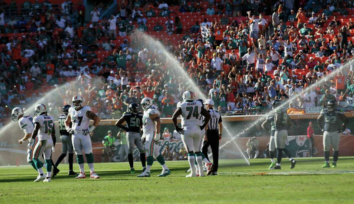 Sprinklers go on during the second half of an NFL football game between the Miami Dolphins and Seattle Seahawks, Sunday, Nov. 25, 2012 in Miami.