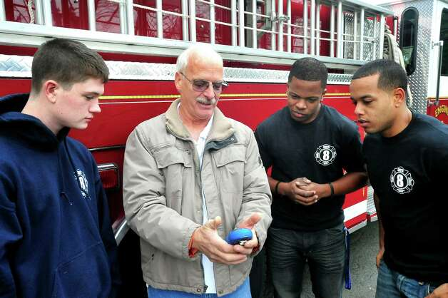 Engine 8 Phoenix Hose Company President Wayne Schlemmer, center, looks at a Carbin Dixoide detector with volunteer firefighters Sean Stoeckle, left, Vincent Mourning and Alan Nunez,right, in Danbury Sunday, Nov. 25, 2012. Photo: Michael Duffy / The News-Times