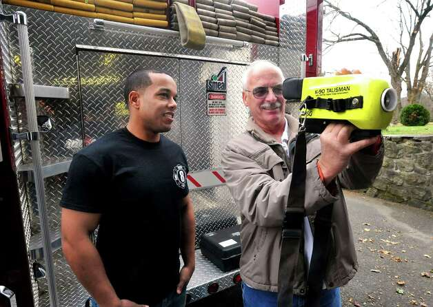 Volunteer firefighter Alan Nunez, left, and Engine 8 Phoenix Hose Company President Wayne Schlemmer use a thermal camera in Danbury Sunday, Nov. 25, 2012. Photo: Michael Duffy / The News-Times