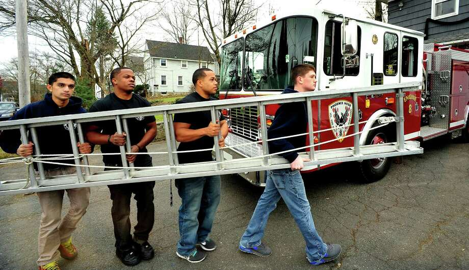 Volunteer firefighters move a ladder at Engine 8 Phoenix Hose Company in Danbury Sunday, Nov. 25, 2012. From left are Dev Patel, Vincent Mourning, Alan Nunez and Sean Stoeckle. Photo: Michael Duffy / The News-Times