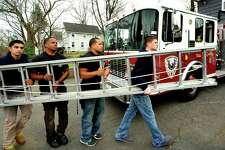 Volunteer firefighters move a ladder at Engine 8 Phoenix Hose Company in Danbury Sunday, Nov. 25, 2012. From left are Dev Patel, Vincent Mourning, Alan Nunez and Sean Stoeckle.