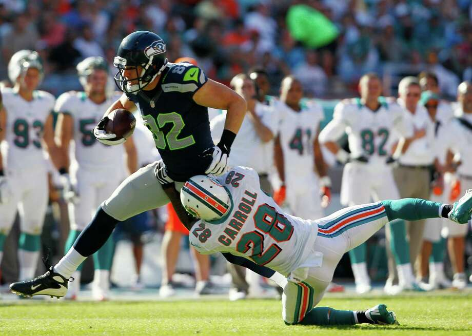 Seattle Seahawks tight end Evan Moore (82) is tackled by Miami Dolphins cornerback Nolan Carroll (28) during the second half of an NFL football game Sunday, Nov. 25, 2012 in Miami. Photo: AP