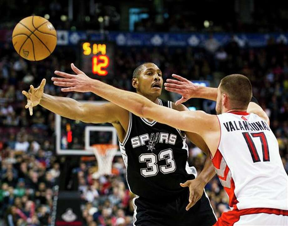 San Antonio Spurs' Boris Diaw passes the ball past Toronto Raptors' Jonas Valanciunas during the second half of an NBA basketball game, Sunday, Nov. 25, 2012, in Toronto. The Spurs won 111-106. (AP Photo/The Canadian Press, Aaron Vincent Elkaim) Photo: Aaron Vincent Elkaim, Associated Press / The Canadian Press