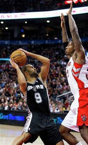 San Antonio Spurs' Tony Parker (9) is challenged by Toronto Raptors' Ed Davis during the second half of an NBA basketball game, Sunday, Nov. 25, 2012, in Toronto. The Spurs won 111-106. (AP Photo/The Canadian Press, Aaron Vincent Elkaim) Photo: Aaron Vincent Elkaim, Associated Press / The Canadian Press