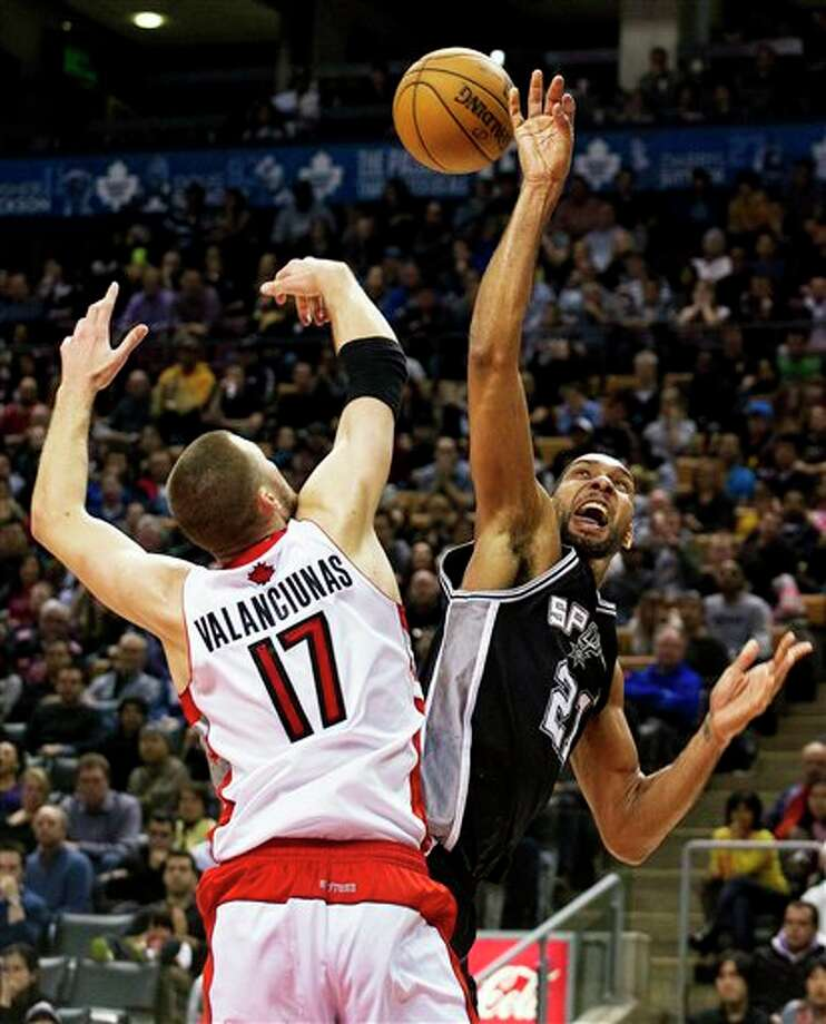 San Antonio Spurs' Tim Duncan (21) is fouled while going to the basket by Toronto Raptors' Jonas Valanciunas during the second half of an NBA basketball game, Sunday, Nov. 25, 2012, in Toronto. The Spurs won 111-106. (AP Photo/The Canadian Press, Aaron Vincent Elkaim) Photo: Aaron Vincent Elkaim, Associated Press / The Canadian Press