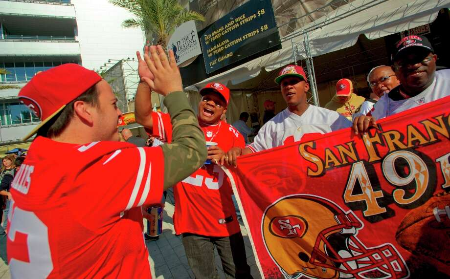 San Francisco 49ers fans Alberto Delgado, Jr., left, high fives Shawn James as they tailgate in Champions Square before a game between the New Orleans Saints and San Francisco 49ers at the Mercedes-Benz Superdome in New Orleans, La., Sunday, Nov. 25, 2012.  (Matthew Hinton / Special to the Chronicle) Photo: MATTHEW HINTON, SFC / ONLINE_YES