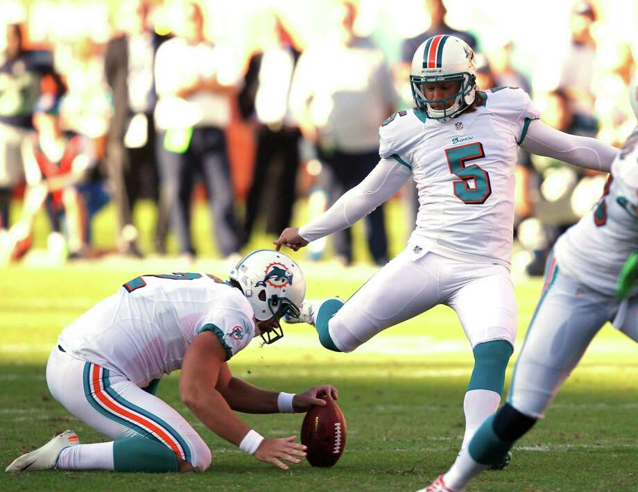 Miami Dolphins kicker Dan Carpenter (5) aims at the ball as Miami Dolphins punter Brandon Fields (2) holds during the second half of an NFL football game against the Seattle Seahawks, Sunday, Nov. 25, 2012 in Miami. Carpenter's field goal won the game for the Dolphins 24-21. Photo: AP