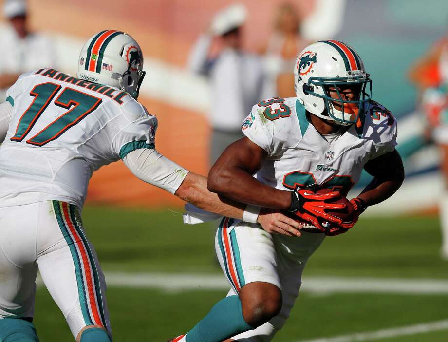 Miami Dolphins quarterback Ryan Tannehill (17) passes the ball to running back Daniel Thomas (33) during the second half of an NFL football game Sunday, Nov. 25, 2012 in Miami. Photo: AP