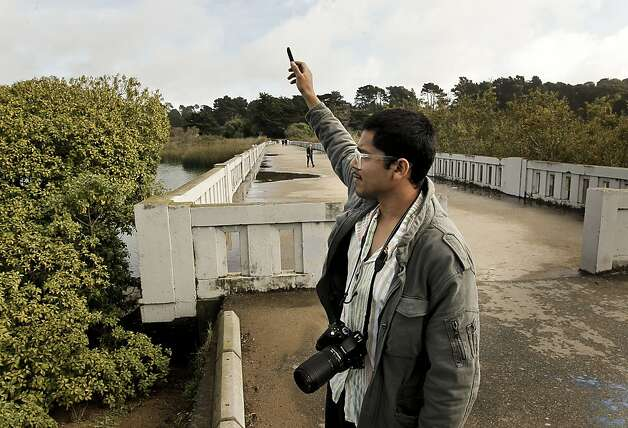 Local birder David Cruz uses a recorded bird call near Lake Merced to try to attract a grackle. Photo: Michael Macor, The Chronicle