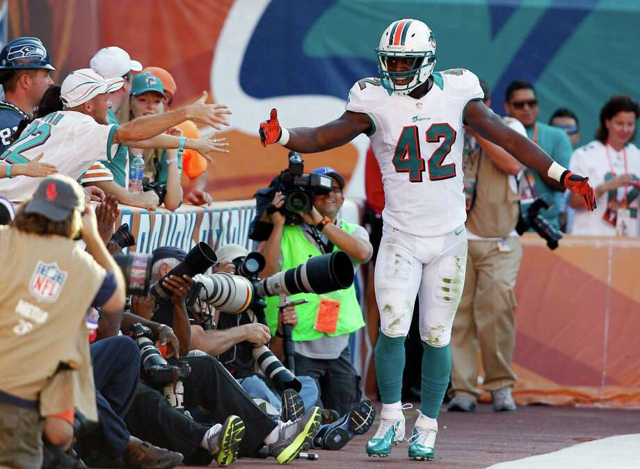 Miami Dolphins fullback Charles Clay (42) shakes hands with fans after scoring a touchdown during the second half of an NFL football game against the Seattle Seahawks, Sunday, Nov. 25, 2012 in Miami. The Dolphins defeated the Seahawks 24-21. Photo: AP