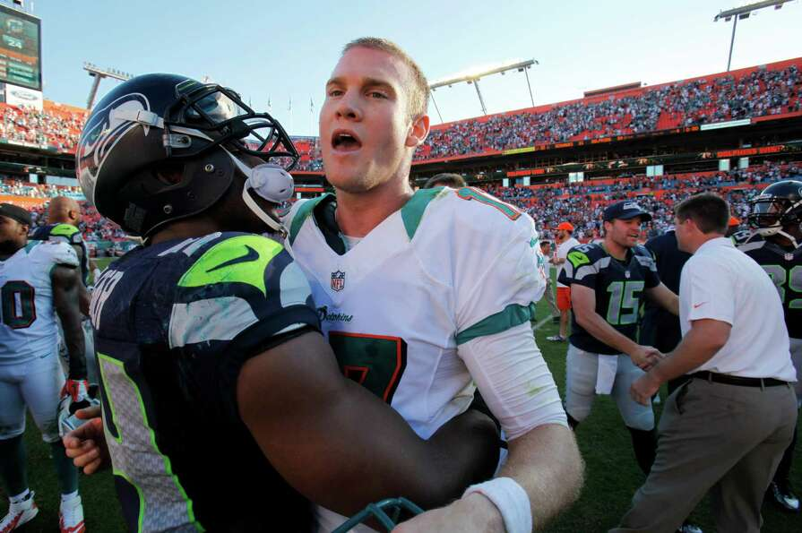 Miami Dolphins quarterback Ryan Tannehill, right, and Seattle Seahawks middle linebacker Bobby Wagne