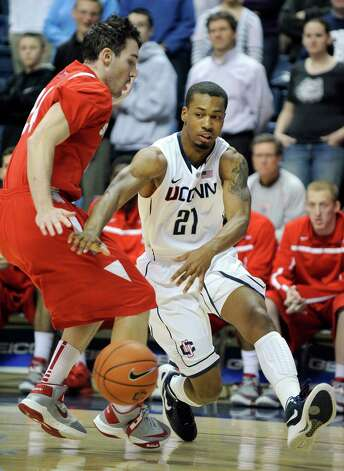 Connecticut's Omar Calhoun, right, drives past Stony Brook's Tommy Brenton during the first half of an NCAA college basketball game in Storrs, Conn., Sunday, Nov. 25, 2012. (AP Photo/Fred Beckham) Photo: Fred Beckham, Associated Press / FR153656 AP