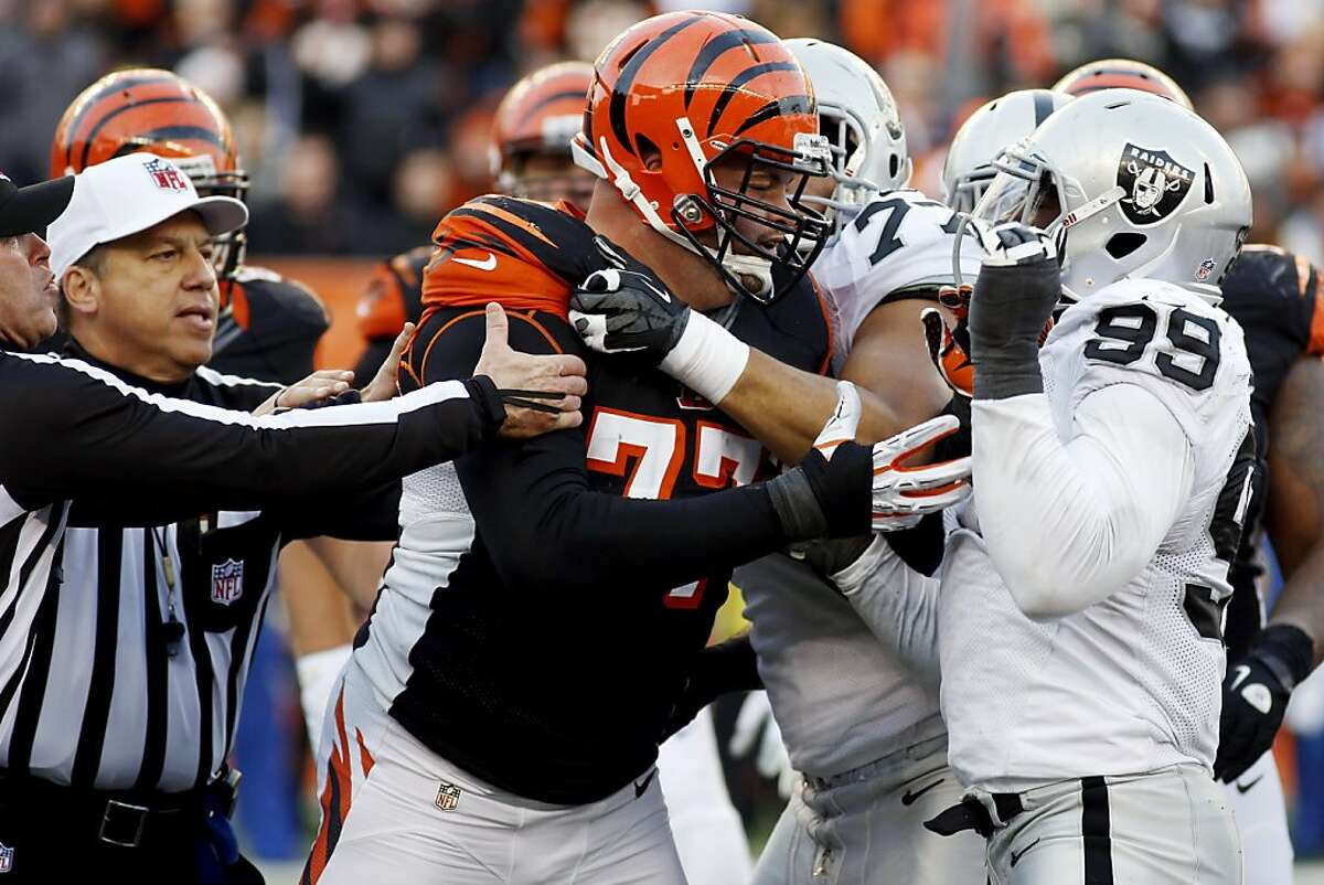 Cincinnati Bengals tackle Andrew Whitworth (77) fights with Oakland Raiders defensive end Lamarr Houston (99) in the second half of an NFL football game, Sunday, Nov. 25, 2012, in Cincinnati. Both players were ejected from the game. The Bengals won 34-10. (AP Photo/David Kohl)