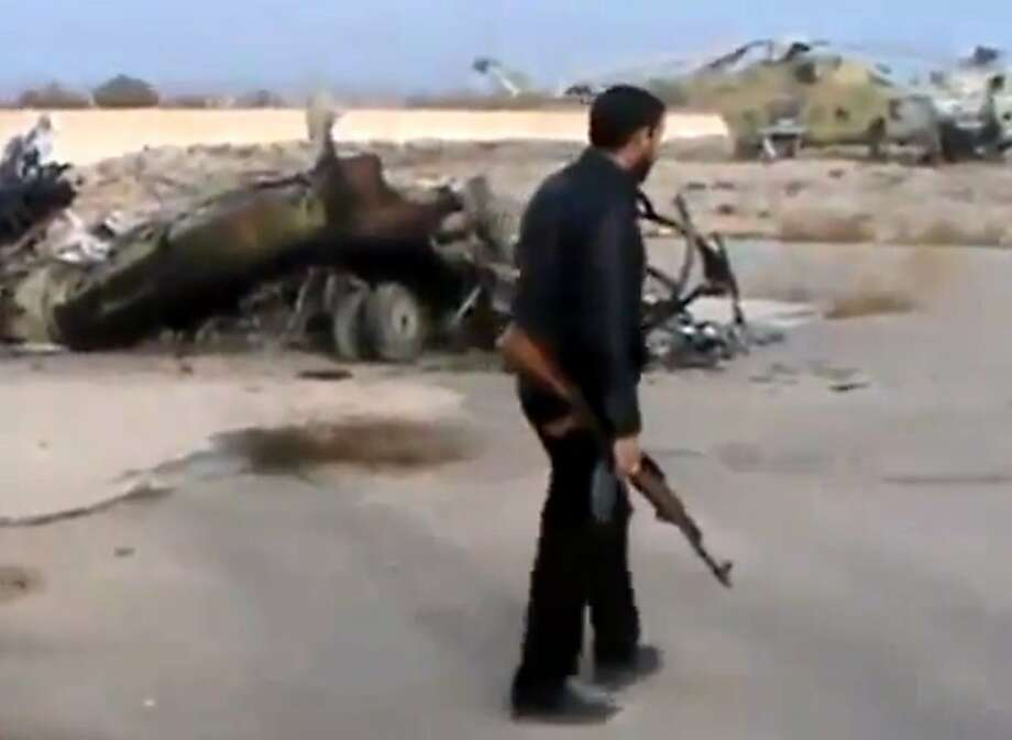 In this image taken from video obtained from the Ugarit News, which has been authenticated based on its contents and other AP reporting, Syrian rebels capture a helicopter air base near the capital Damascus after fierce fighting in Syria, on Sunday, Nov. 25, 2012. The takeover claim showed how rebels are advancing in the area of the capital, though they are badly outgunned by Assad's forces, making inroads where Assad's power was once unchallenged. Rebels have also been able to fire mortar rounds into Damascus recently. (AP Photo/Ugarit News via AP video) Photo: Uncredited, Associated Press