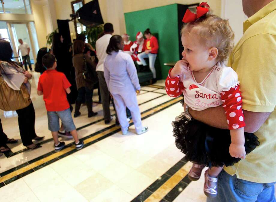 Bella Zaccardo is held by her father, Fabian, as she waits in line to have pictures taken with Santa at Sugar Land Town Square Sunday, Nov. 25, 2012, in Sugar Land. The free photos will be offered on Sundays through December 16. Photo: Brett Coomer, Houston Chronicle / © 2012 Houston Chronicle