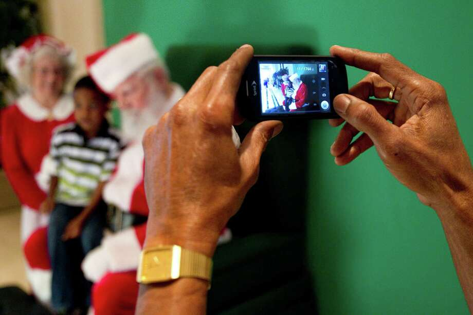 Anthony Prescod takes a photo of his son, A.J., sitting on Santa's lap at Sugar Land Town Square Sunday, Nov. 25, 2012, in Sugar Land. The free photos will be offered on Sundays through December 16. Photo: Brett Coomer, Houston Chronicle / © 2012 Houston Chronicle