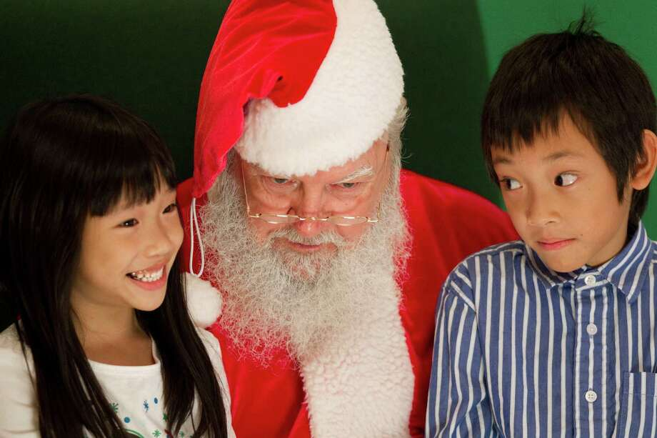 Santa listens to Jasmine and Jared Ho as they have Christmas pictures taken at Sugar Land Town Square Sunday, Nov. 25, 2012, in Sugar Land. The free photos will be offered on Sundays through December 16. Photo: Brett Coomer, Houston Chronicle / © 2012 Houston Chronicle