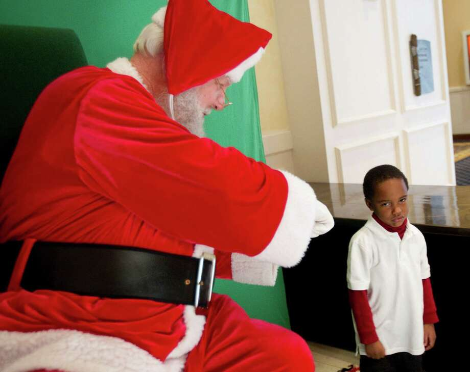 Santa reaches out to get a fist bump from Brycen Sylvester before having Christmas pictures taken at Sugar Land Town Square Sunday, Nov. 25, 2012, in Sugar Land. The free photos will be offered on Sundays through December 16. Photo: Brett Coomer, Houston Chronicle / © 2012 Houston Chronicle