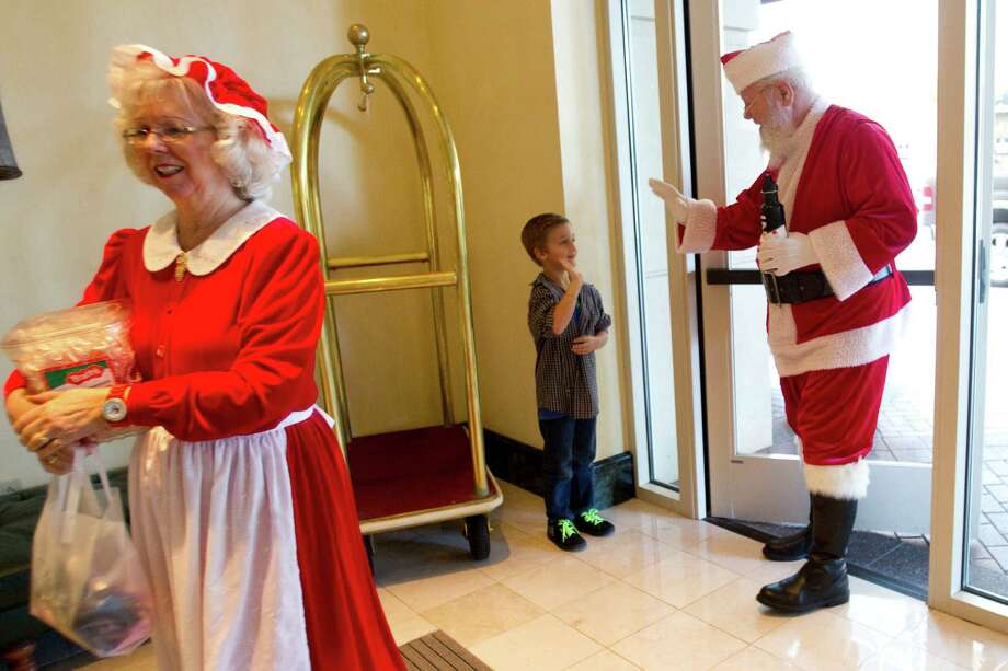 Hayes Brown waves to Santa and Mrs. Claus as they arrive to the Sugar Land Marriott for free Christmas pictures taken Sunday, Nov. 25, 2012, in Sugar Land. The free photos will be offered on Sundays through December 16. Photo: Brett Coomer, Houston Chronicle / © 2012 Houston Chronicle