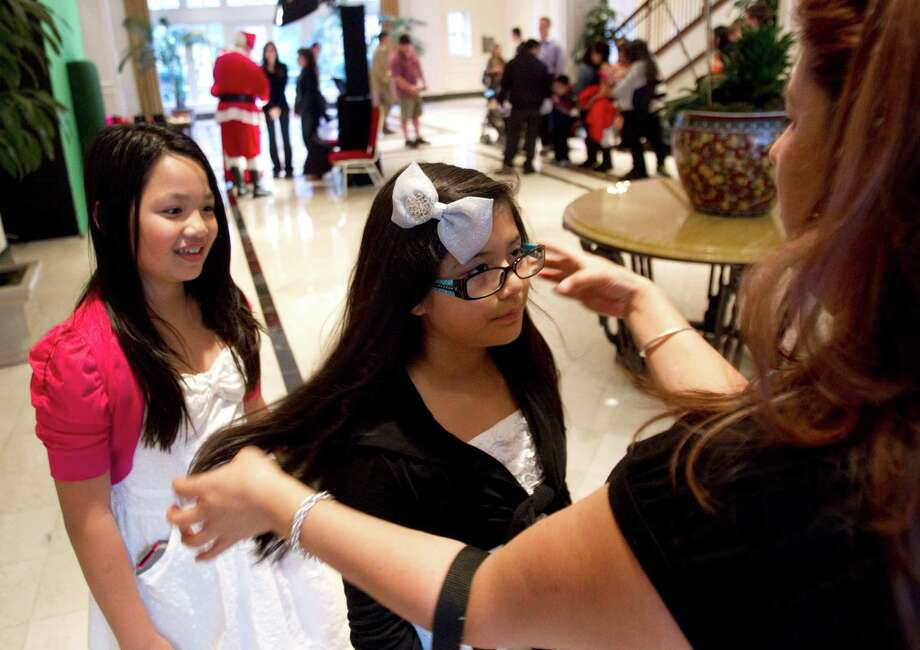Susana Carranza, right, fixes Paulina Carranza's hair, as Amy Nguyen watches, while waiting in line to have free Christmas pictures taken at Sugar Land Town Square Sunday, Nov. 25, 2012, in Sugar Land. The free photos will be offered on Sundays through December 16. Photo: Brett Coomer, Houston Chronicle / © 2012 Houston Chronicle