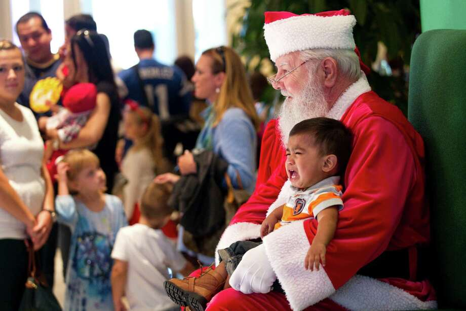 Maximiliano Alvarez, 1 1/2, cries while sitting in Santa's lap while having free Christmas pictures taken at Sugar Land Town Square Sunday, Nov. 25, 2012, in Sugar Land. The free photos will be offered on Sundays through December 16. Photo: Brett Coomer, Houston Chronicle / © 2012 Houston Chronicle
