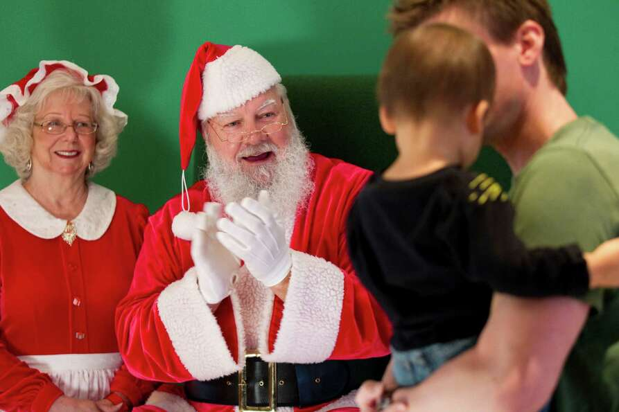 Santa and Mrs. Claus try to coax a shy child to sit and have a picture taken with them at Sugar Land