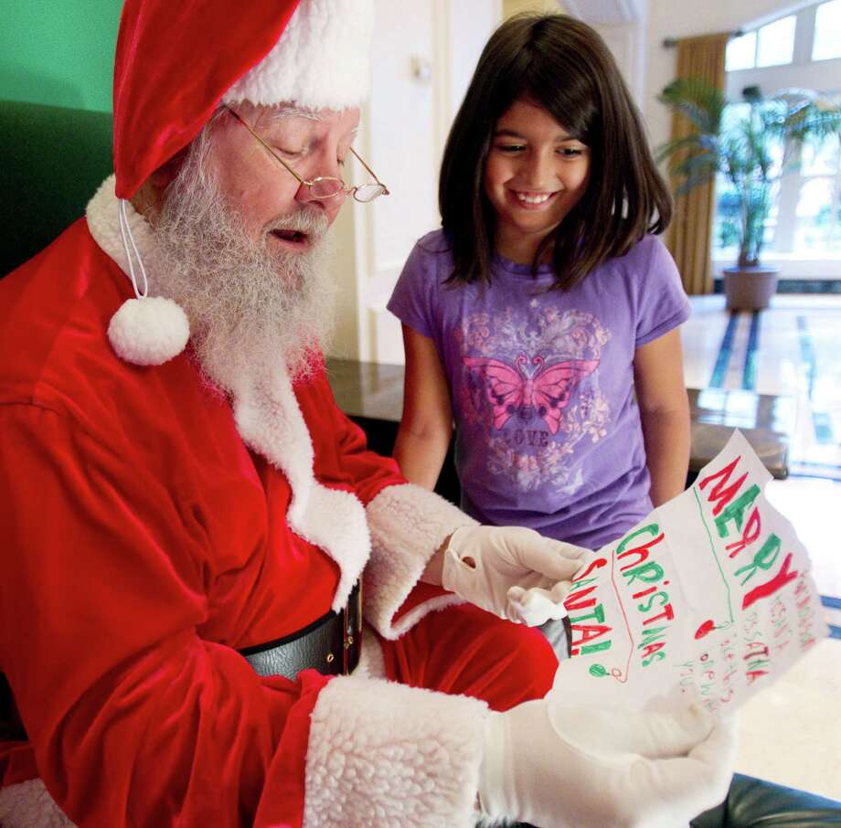Madison Delgado gives Santa a note before having her picture taken with him at Sugar Land Town Square Sunday, Nov. 25, 2012, in Sugar Land. The free photos will be offered on Sundays through December 16. Photo: Brett Coomer, Houston Chronicle / © 2012 Houston Chronicle