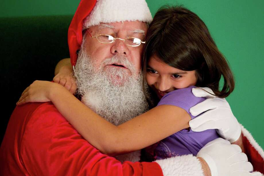 Madison Delgado hugs Santa a note before having her picture taken with him at Sugar Land Town Square Sunday, Nov. 25, 2012, in Sugar Land. The free photos will be offered on Sundays through December 16. Photo: Brett Coomer, Houston Chronicle / © 2012 Houston Chronicle