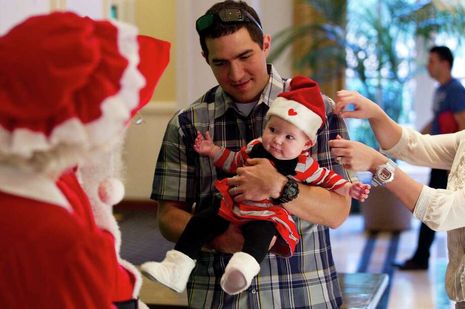 David Morris carries his daughter, Reyna, to have her picture taken with Santa at Sugar Land Town Square Sunday, Nov. 25, 2012, in Sugar Land. The free photos will be offered on Sundays through December 16. Photo: Brett Coomer, Houston Chronicle / © 2012 Houston Chronicle